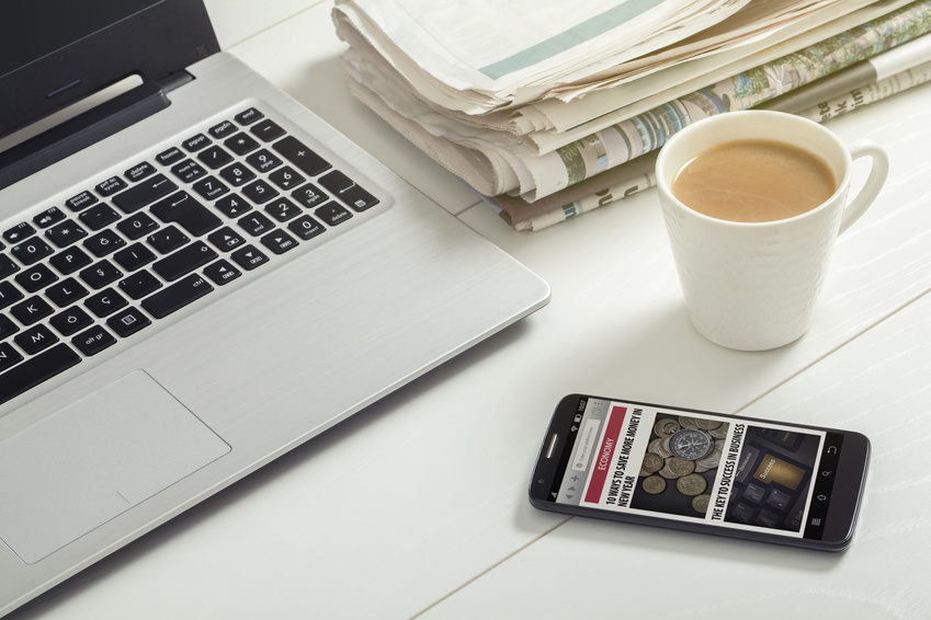 news on smartphone, laptop, milk coffee and newspapers on office desktop